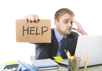 young desperate businessman holding help sign looking worried suffering work stress at computer desk