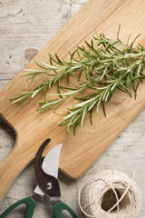 Chopping board with rosemary lying on top of a worn wooden surfa