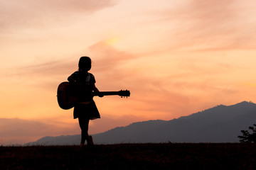 a silhouette of a girls standing with her guitar.