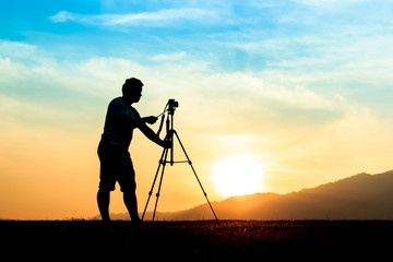Silhouette of a young photographer during the sunset.