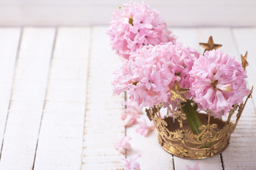 Flowers hyacinths in decorative crown on white  painted wooden p