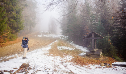 Female tourist/photograher is taking picture using professional camera during her hike on the mountain trail in the forest on a foggy winter day.