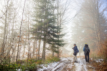 Man and woman hikers walking up on foggy forest mountain trail in winter/late autumn. Female photographer holding the camera and smiling.