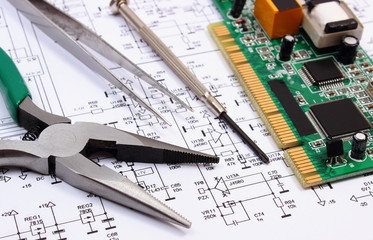Printed circuit board and precision tools on diagram of electronics, technology