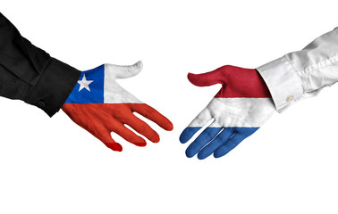Chile and Netherlands leaders shaking hands on a deal agreement