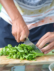 Man cutting green salad on the wooden board