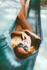 young beautiful girl in sunglasses denim shorts and shirt posing while lying on a hammock, beautiful woman, brunette resting on vacation at the beach, relax, outdoor portrait