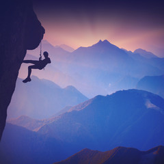 Climber on a cliff against misty mountains. Vintage colors