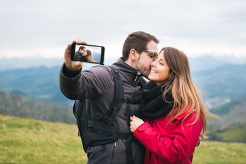 Young couple in love  taking selfie while kissing, hiking outdoor on vacation. Rural holyday relaxing gateaway.