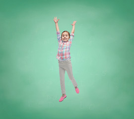 happy little girl jumping in air over school board
