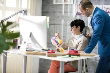 Designer with colleague at design studio.