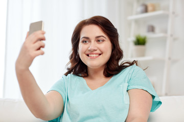 happy plus size woman with smartphone at home