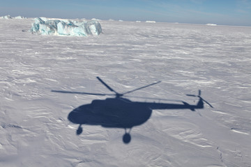 Poster Pole Aerial view of iceberg in frozen Arctic Ocean and helicopter shadow