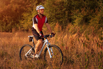 Man is riding a mountain bike in the field
