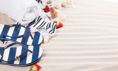 Marine sandal, flip- flop, swimsuit and summer accessories on sand with tropical beach background