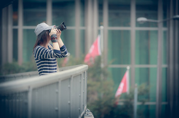 Girl holding a camera and  shooting in City