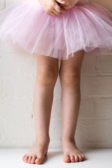 Little girl in pink tutu standing with hands clasped against white brick wall (cropped)