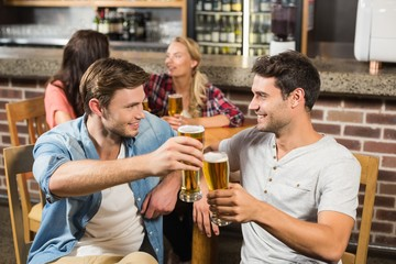 Men toasting in front while women talk behind
