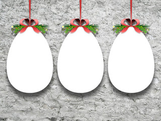 Close-up of three hanged blank Easter egg frames with ribbon against rough wall background