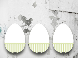 Close-up of three hanged blank Easter egg frames with clips against grey scratched concrete wall background