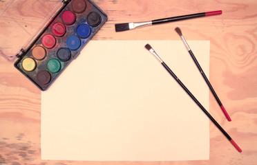Flat lay - watercolors, paintbrushes, paper, wooden desk (vintage color shift)