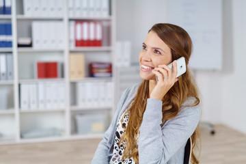 lächelnde, entspannte frau im büro telefoniert mit ihrem handy