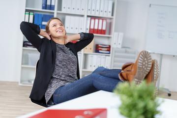 zufriedene frau legt im büro die füße auf den tisch