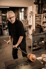 Glassblower forming molten glass in his worshop