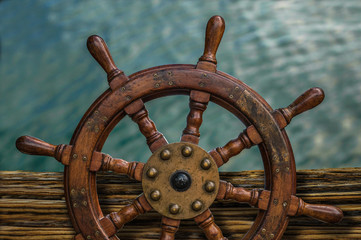 Ships Wheel Against Ocean Water
