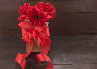 Red gerbera flowers with ribbon are in the bag, on the wooden ba
