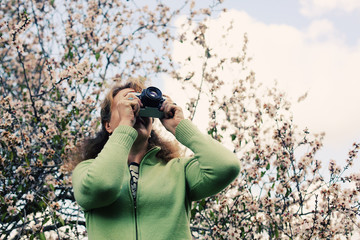 Woman with vintage retro camera walking in the park