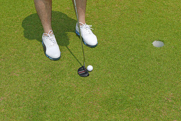 Golf player with white shoes holding a club with golf ball near a hole