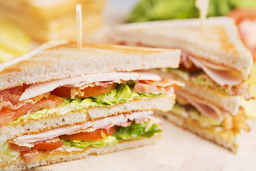 Club sandwich on a rustic table in bright light