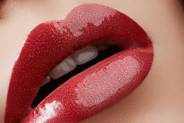 Close-up of female lips with bright makeup. Macro of woman's face. Fashion lip make-up with red gloss