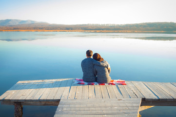 Loving couple relaxing on the dock on the big lake