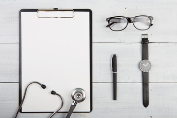 Workplace of doctor - stethoscope, medicine clipboard, glasses a