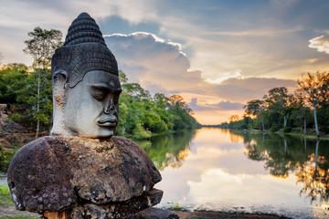 Fototapete - Stone Asura and sunset over moat surrounding Angkor, Cambodia
