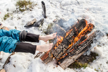 A man warms his barefoot feet near the fire in the pine forest covered with snow in winter