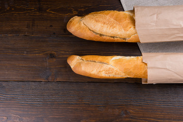 Twin loaves of french bread in bags