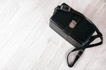 Vintage black leather case on a wooden floor