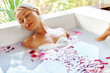 Beauty Woman Spa Body Care Treatment. Closeup Portrait Of Beautiful Smiling Model Girl Relaxing In Flower Bath Tub In Salon. Skin Care, Cleansing Procedure Concept. Healthy Lifestyle, Wellness