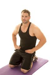 strong man in black tank kneel