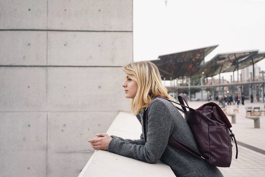 Attractive blonde student thinking about new business idea while looking at the urban landscape.