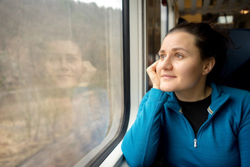 Portrait of young woman traveling by a train.