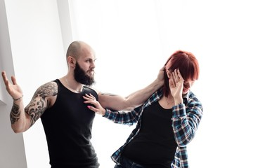 Muscular tattooed man beating up his wife.