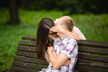 Portrait of attractive young girl kissing boyfriend and closing their lips by hand