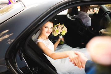 Happy groom helping his beautiful bride out of wedding car.