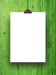 Close-up of one hanged blank frame with clip against green painted wood
