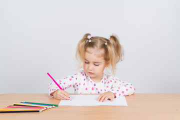 Little girl draws at table pencils.