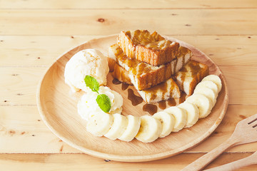 French toast topped with sliced bananas, nuts, cream cheese sauce and caramel syrup.